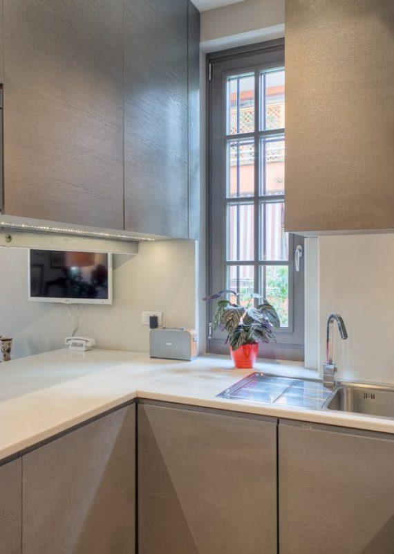 cucina in legno laccato a poro aperto e piano in corian